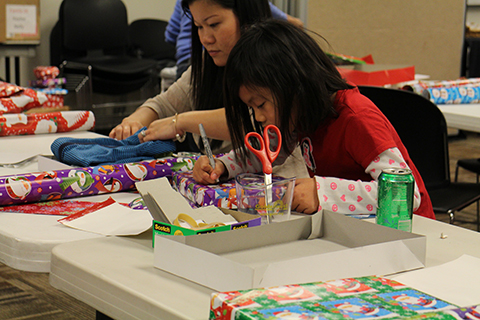 Volunteers wrapping presents for families in need