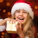 A young child wearing a Santa hat holding a gift and smiling